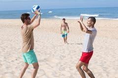 Agrupe a las muchachas alegres jovenes que juegan a voleibol en la playa imagen de archivo libre de regalías
