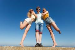 Agrupe a las muchachas del muchacho dos de los amigos que se divierten al aire libre Foto de archivo