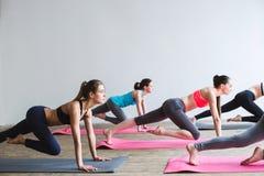 Agrupe a las mujeres en el piso del gimnasio de los deportes que hace pectorales Imágenes de archivo libres de regalías