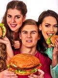 Agrupe los alimentos de preparación rápida de la hamburguesa con el jamón en manos de la gente Fotos de archivo libres de regalías