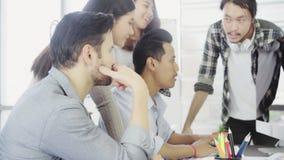 Agrupe a los compañeros de trabajo jovenes junto que discuten proyecto creativo durante colegas modernos del proceso del trabajo  metrajes