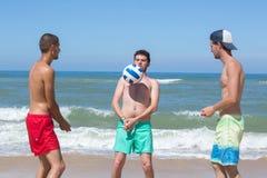 Agrupe a los hombres alegres jovenes que juegan a voleibol en la playa foto de archivo