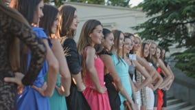 Agrupe modelos nos vestidos que estão na fileira e que levantam nas etapas filme