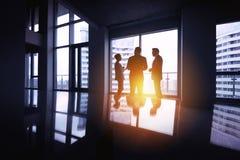 Agrupe o conceito de janela grande do escritório das silhuetas três dos homens de negócios Fotografia de Stock