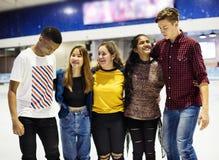Agrupe o tiro de amigos adolescentes na pista da patinagem no gelo da pista Imagens de Stock
