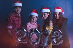 Agrupe os amigos novos asiáticos que guardam o fraseio 2018 party junto o ce Imagens de Stock Royalty Free