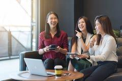Agrupe a tres mujeres que se encuentran en una cafetería que charla a cada othe Foto de archivo