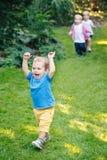 Agrupe um retrato de três crianças bonitos adoráveis louras caucasianos brancas que jogam a corrida no jardim do parque fora Fotografia de Stock Royalty Free