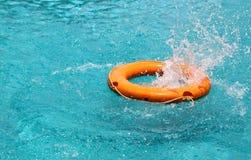 Agua anaranjada del chapoteo de la boya de vida en la piscina azul Imagen de archivo libre de regalías