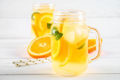 Agua anaranjada del detox en tarros de albañil en una tabla de madera blanca Comida sana, bebidas Imagenes de archivo