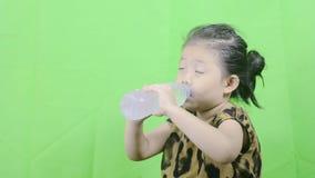 Agua asiática linda de la bebida de la niña en una botella clara metrajes