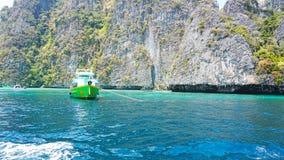 Agua azul, colinas verdes y rocas escarpadas Las velas del barco cerca de la isla Barco con los turistas en la bah fotos de archivo libres de regalías