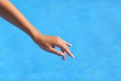 Agua azul conmovedora de la mano hermosa de la mujer en una piscina Imagen de archivo