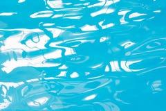 Agua azul de la piscina con reflexiones del sol Modelo borroso extracto Imagen de archivo