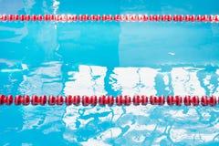 Agua azul de la piscina y marcador de carril rojo de natación en piscina con reflexiones del sol Modelo abstracto Fotos de archivo libres de regalías