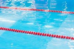 Agua azul de la piscina y marcador de carril rojo de natación en piscina con reflexiones del sol Modelo abstracto Fotografía de archivo
