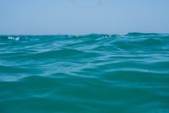 Agua azul del océano del claro de Marin con las ondas y cielo con las nubes tirado del agua Foto de archivo