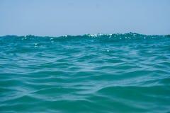 Agua azul del océano del claro de Marin con las ondas y cielo con las nubes tirado del agua Fotos de archivo