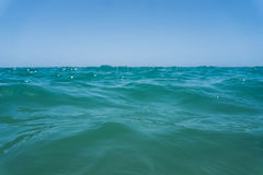 Agua azul del océano del claro de Marin con las ondas y cielo con las nubes tirado del agua Adultos jovenes Fotografía de archivo