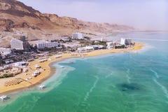 Agua azul en el mar muerto en el primero plano en el fondo de la ciudad de vacaciones de Ein Bokek en el medio del desierto adent fotos de archivo