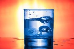 Agua azul en un vidrio en un fondo luminoso rojo Foto de archivo libre de regalías