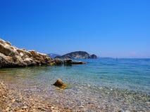 Agua azul y rocas en el verano mediterráneo imagen de archivo