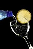 Agua burbujeante que es vertida en un vidrio Fotografía de archivo libre de regalías