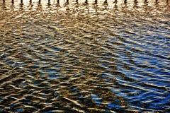 Agua chispeante azul y amarilla en una piscina fotos de archivo