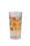 Agua chispeante en un vidrio con el estampado de flores aislado en un whi Foto de archivo libre de regalías