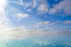 Agua, cielo y nubes mullidas Imagen de archivo libre de regalías