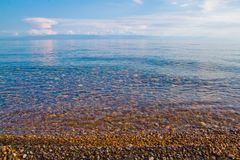 Agua clara de la turquesa, playa pedregosa y cielo azul como fondo foto de archivo libre de regalías