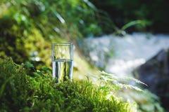 Agua clara en un vidrio claro contra un fondo del musgo verde con un río de la montaña en el fondo Alimento sano Imagen de archivo