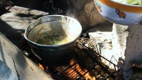 Agua cocinada en el fuego de madera en el pote de aluminio viejo frecuencia intermedia metrajes