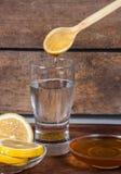 Agua con el limón y la miel foto de archivo libre de regalías
