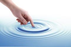 Agua conmovedora de la mano de la mujer Foto de archivo