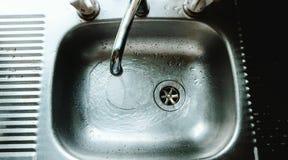 Agua corriente del golpecito en fregadero Fotografía de archivo libre de regalías