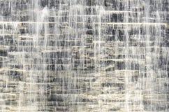 Agua corriente sobre la pared de piedra gris oscuro Foto de archivo