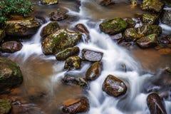 Agua corriente a través del río de la roca en la exposición larga Imágenes de archivo libres de regalías