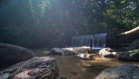 Agua cristalina con la cascada en el bosque Fotos de archivo libres de regalías
