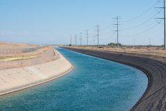 Agua de abastecimiento del canal de las montañas a la ciudad en el desierto imagen de archivo