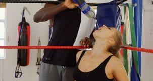 Agua de alimentación masculina del instructor al boxeador de sexo femenino en el ring de boxeo 4k almacen de video