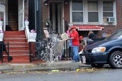 Agua de bombeo de la gente fuera del sótano del edificio Foto de archivo libre de regalías