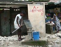 Agua de bombeo en el casquillo Haitien Foto de archivo