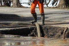 Agua de bombeo fuera del hoyo al eliminar un accidente: ruptura de los tubos con la agua fría Foto de archivo libre de regalías