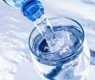 Agua de colada de la botella en el vidrio foto de archivo libre de regalías