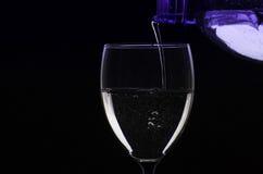 Agua de colada de la botella en el vidrio Foto de archivo