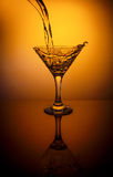 Agua de colada de la botella en el vidrio en fondo anaranjado Fotografía de archivo libre de regalías