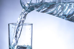 Agua de colada de la jarra en un vidrio Imagen de archivo