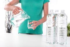 Agua de colada de la mujer en un vidrio Fotografía de archivo