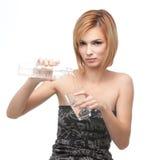 Agua de colada de la mujer joven en un vidrio Fotografía de archivo